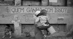 Quem ganha com isto? é a pergunta presente na frase pixada na parede. Esta fotografia expressa a desigualdade social em nosso país. <br/> Um pai carregando seu filho em meio a miséria social. <br/> <br/> Palavras-chave: desigualdade social, miséria, periferia, cidadania, poder, ideologia, política.