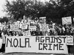 """11 de janeiro de 2007 - Poydras Street, New Orleans, LA. nos Estados Unidos. """"Silence is Violence. Protest against the rise in violent crime."""" <br/> <br/> """"Silêncio é violência. Protesto contra o aumento da violência e do crime"""" <br/> <br/> Na imagem passeata de manifestantes com os seguintes dizeres:""""Nova Orleans contra o crime"""", """"vocês vivem, nós morremos"""". <br/> <br/> Palavras-chave:direito, cidadania, movimentos sociais, classes sociais, protesto, violência."""