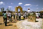 """Turistas no portal de entrada do Arraial. <br/> """"...em poucos anos o arraial de Canudos se firmou na região (sul da Bahia) como um contestado, passando a reunir cada vez mais sertanejos que lutavam para mudar suas condições de vida fugindo da miséria e dominação dos grandes latifundiários."""" O arraial original está submerso pelas águas do açude de Cocorobó desde 1969. A atual canudos está a 10 km de distância deste. <br/> <br/> Palavras-chave: Canudos, Antônio Conselheiro, revolta popular, direito, cidadania, movimentos sociais, poder, classes sociais, latifúndio, concentração de terra"""